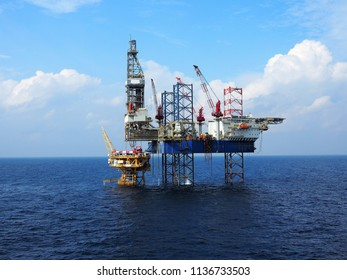 Jack up drilling rig operates over offshore wellhead platform with blue sea background.