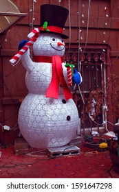 Jack frost, snow man Christmas decoration with black hat and red scarf with presents in a yard in the crown heights section of Brooklyn NY on a winter day December 17 2019