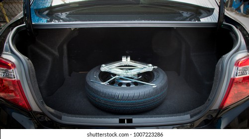jack lifting and a spare wheel in rear of car