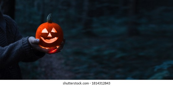 Jack o lantern glowing with moonlight on in eerie night forest. Halloween bokeh background with burning orange pumpkin that a men holds in his hands. Happy Halloween banner. Copy space for text
