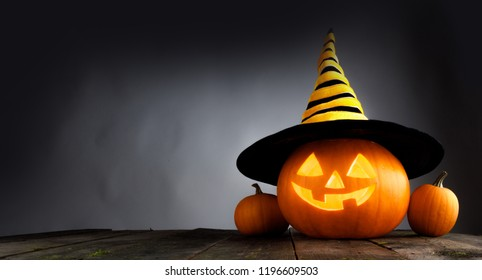 Jack O Lantern Halloween pumpkin with witches hat on wooden table over dark background