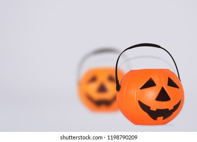 Jack O' Lantern Halloween pumpkin pail on grey background. Orange plastic Trick Or Treat candy bucket made from resin with handle.