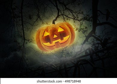Jack O Lantern pumpkin over old fence, dead tree, moon and cloudy sky, Mystery background, Halloween concept