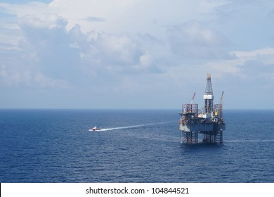 Jack up oil drilling rig and a crew boat