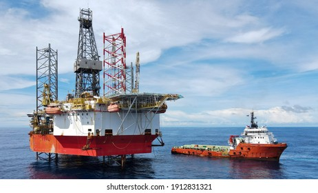 A jack up rig with an anchor handling vessel during cargo operation at sea.