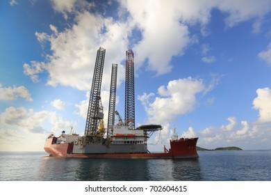 Jack up rig legs Transportation by heavy lift vessel orange color on the sea with blue sky