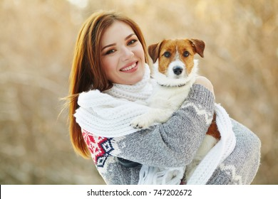 Jack Russell Terrier dog with owner woman in the winter outdoors