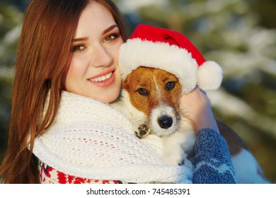 Jack Russell Terrier dog in red Santa hat with owner woman in the winter outdoors