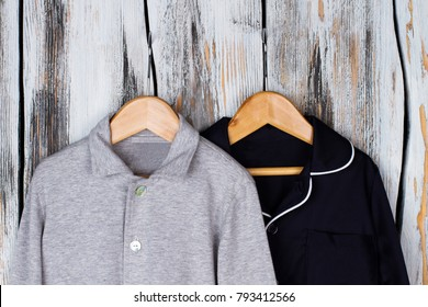 Jackets on wooden hangers. Gray melange and navy pajama tops. Boys wardrobe, sleepwear and loungewear.