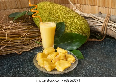 Jackfruit juice in a glass. Fresh sweet jackfruit slices on a glass plate. Exotic ripe jackfruit ready for eat. Sweet jackfruit cocktail. Organic fruit concept. Tropical fruit. Selective focus.