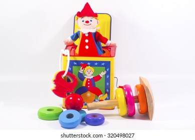 Jack-in-the-box toy and round wooden painted o-rings to stack for kids.