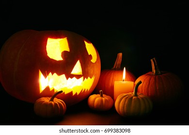 Jack-o-lantern, burning candle and several ripe pumpkins in the dark