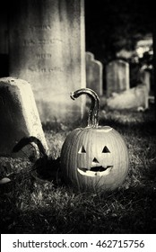 A jack-o'-lantern pumpkin in a graveyard surrounded by old headstones. Black and white filter with film grain and vignette applied.