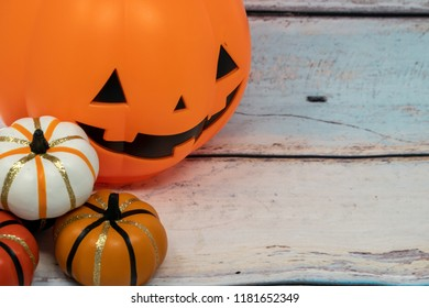 Jack-o-lantern and small pumpkin decorations over a blue wooden background for Halloween and autumn.