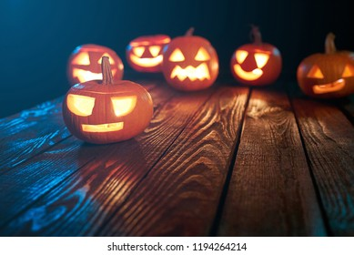 Jack-o-latern Halloween pumpkins on wooden planks, one pumkin ahead of others, copy space in foreground