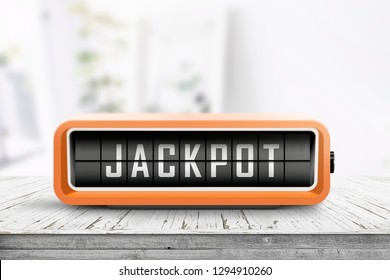 Jackpot message on a retro alarm device in a bright room on a wooden desk