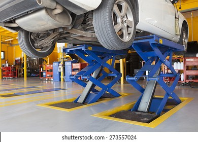 jacks, scissor cranes lift the car in garage