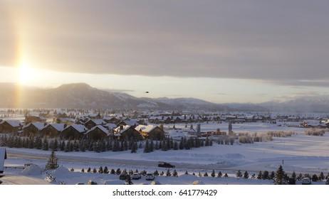 JACKSON HOLE, WY – DECEMBER 23, 2016: Sunrise over Teton Village at Jackson Hole ski resort, causes vertical rainbow. Black bird flies overhead.