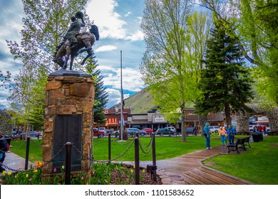 JACKSON HOLE, WYOMING, USA - MAY 23, 2018: Outdoor view of tourist walking in a park close to a bronze statue of cowboy on horse in the Town Square in Jackson Wyoming