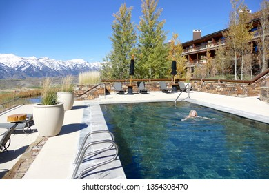 Jackson Hole, Wyoming USA / Oct 8, 2016: Amangani Resort and hotel outdoor swimming pool with one female swimmer, snow capped mountain range in background