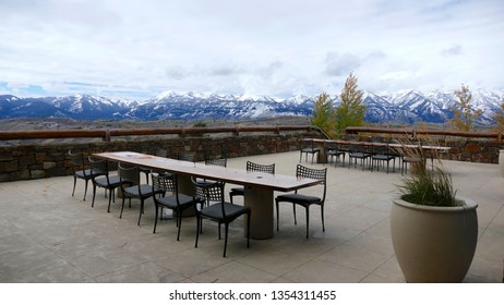 Jackson Hole, Wyoming, USA / Oct 8, 2016: Amangani Hotel and resort outdoor patio, long table, chairs, potted plant, snow covered mountain range in background