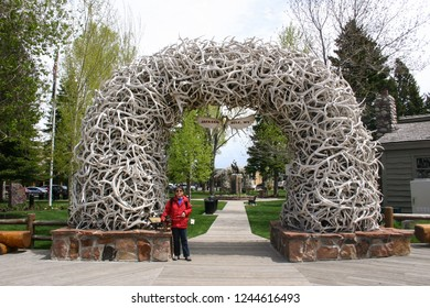 JACKSON HOLE, WYOMING-MAY 23, 2013:  Tourists love to pose for pictures before the Elk Antler Arch at George Washington Memorial Park - gateway to the Tetons and Yellowstone National Parks.