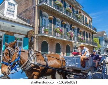 Jackson Square, New Orleans, Louisiana, USA - March 31, 2018: Horse-drawn carriage with tourists the French Quarter of New Orleans. Creole style house is in the background. Horizontal photo. Blue sky.