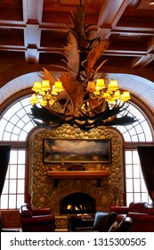 Jackson, Wyoming, United States - February 22, 2009: Moose Antler chandelier with fireplace and leather chairs in a western lodge Wyoming