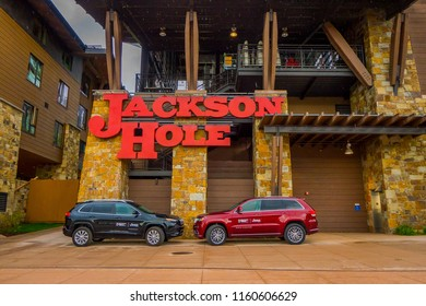 JACKSON, WYOMING, USA, JUNE, 07, 2018: Outdoor view of two cars parked in from of the gorgeous wooden and stoned hotel. The somewhat Tudor-style building was the first luxury hotel in Jackson