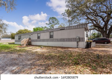 Jacksonville, Florida / USA - April 3 2020: Mobile home with a large tree nearby