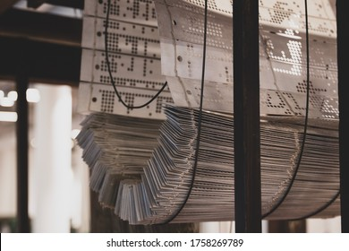 Jacquard head, harnesses and set of cards or punched paper. Old jacquard machine, looms for jacquard weaves, enabling to manufacture complex and outstanding linen damasks. Jacquard loom punch card.