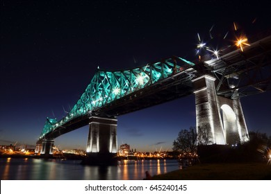 Jacques Cartier Bridge Illumination in Montreal, reflection in water. Montreal's 375th anniversary. luminous colorful interactive Jacques Cartier Bridge. Bridge panoramic colorful silhouette by night.