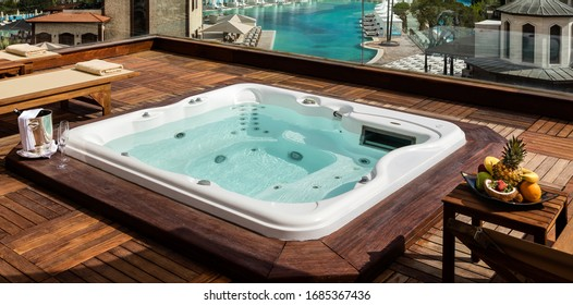 Jacuzzi on the terrace of a Luxury Hotel, wine glasses and fruit platter. Spa complex, vacation and traveling concept