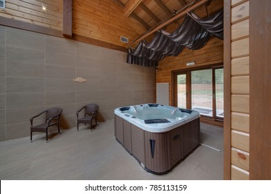 A jacuzzi with red illumination, wattled chairs and a big window