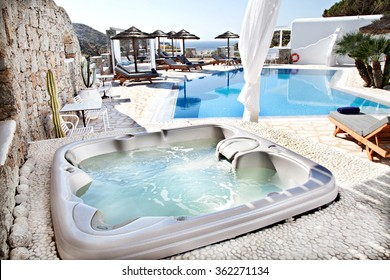 jacuzzi with a swimming pool in background