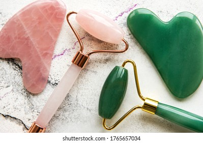 Jade face rollers for beauty facial massage therapy. Flat lay on marble background
