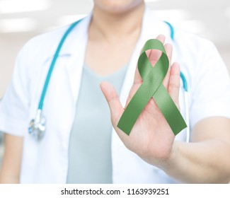 Jade green or Emerald color ribbon awareness in doctor's hand for Liver Cancer and Hepatitis B disease, healthcare medical concept