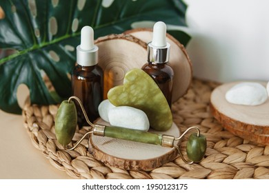 Jade Gua sha scraper and roller face massager bottles of cosmetic serum for the face on wooden stands