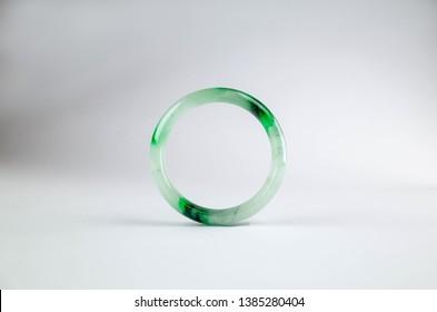 A jadeite jade bangle with streaks of imperial green jade