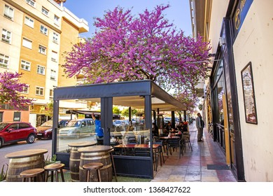 JAEN, SPAIN - 29 March 2019: A cozy street with restaurants and bars full of visitors during lunch time in Jaen