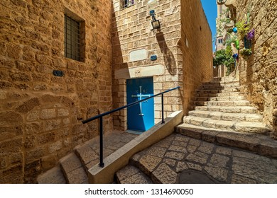 JAFFA, ISRAEL - JULY 18, 2018: Stone stairs on narrow street among medieval walls in small town of Jaffa - ancient port south of Tel-Aviv, popular tourist destination for its beauty and rich history.