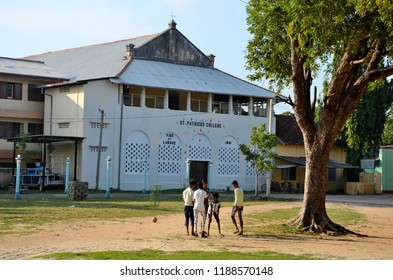 Jaffna, Sri Lanka - February 17, 2017: A group of young boys play football in the compound of the St Mary's Cathedral Catholic church. A large tree in the foreground with St Patrick's College in back.