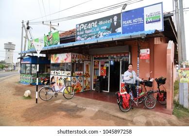 JAFFNA,SRI LANKA - JANUARY 30.2018: female cyclist standing with loaded folding bike  on January 30,2018 in Jaffna, Sri Lanka