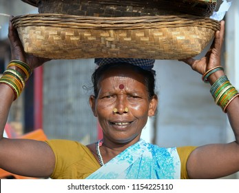 JAGDALPUR, CHHATTISGARH / INDIA - DEC 10, 2016: Indian Adivasi tribal woman with bindi and two golden nose studs carries on her head various baskets to the Sanjay Market, on Dec 10, 2016.