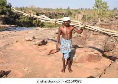 JAGDALPUR , INDIA - DECEMBER 12 2016 : Bastar tribal man carrying woods and axe near tamra ghoomar waterfalls , Bastar.