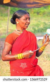 Jagdalpur,23,October, 2012:  Portrait of  happy tribal woman in traditional red saree and  jewllery  holding sickle in her tattooed  hands at Haat Weekly Bazaar,Bastar, Chhattisgarh,India,Asia
