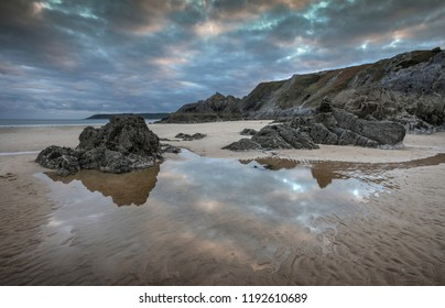 Jagged landscape and beach pool reflections on Three Cliffs Bay looking towards the Great Tor and Oxwich Bay, Gower