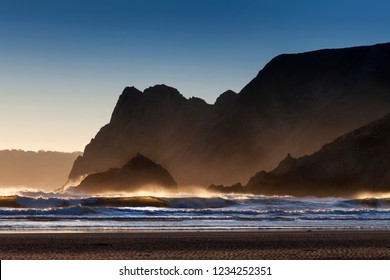 Jagged landscape and crashing waves on the Great Tor at Three Cliffs Bay, Gower, Swansea, UK