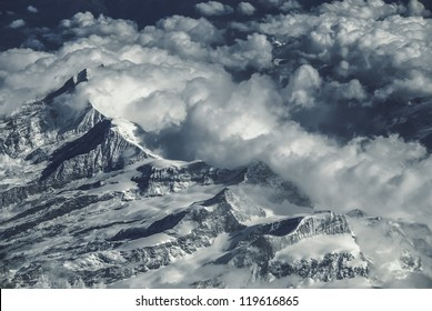 The jagged peaks of the mountain range appear through the clouds blocking their flow