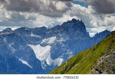 Jagged sawtooth crest of Sexten Sesto Dolomites peak Dreischusterspitze Punta dei Tre Scarperi towering above sunny grassy green slopes of Carnic Alps main ridge Belluno South Tyrol Tirol Italy Europe